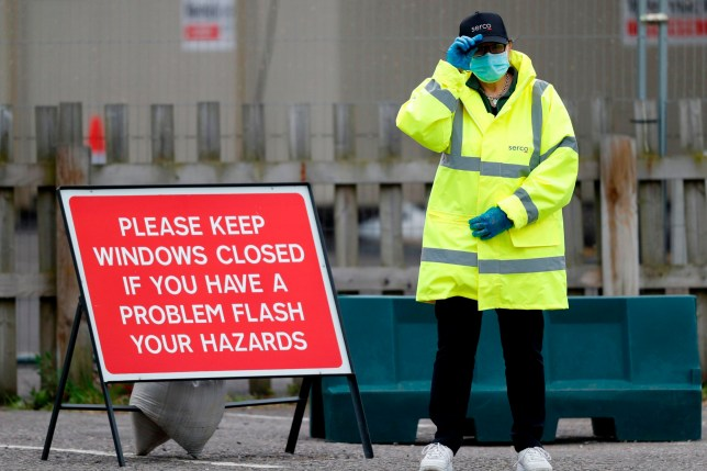 A steward stands ready to help people arriving at the coronavirus COVID-19 testing centre set up in the car park of Chessington World of Adventures, south of London on May 10, 2020, during the national lockdown due to the novel coronavirus COVID-19 pandemic. - The Prime Minister will on Sunday unveil a new alert system to monitor the coronavirus outbreak but maintain a nationwide lockdown as Britain's death toll, the highest in Europe, continues to mount. (Photo by Adrian DENNIS / AFP) (Photo by ADRIAN DENNIS/AFP via Getty Images)