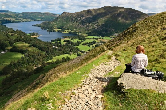 A woman hill walker looks out over Ullswater and Patterdale in the English Lake District.