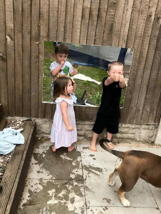 Young Arlo and Arabella playing with neighbour Leo through their perspex window