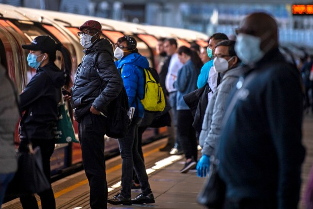 Passengers wearing face masks on a platform at Canning Town underground station in London. PA Photo. Picture date: Tuesday May 12, 2020. Passengers travelling on public transport in the capital are being told to wear face coverings, with Transport for London (TfL) saying that the measure could prevent people with coronavirus infecting others. See PA story HEALTH Coronavirus. Photo credit should read: Victoria Jones/PA Wire