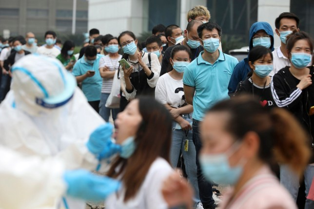 Workers line up for medical workers to take swabs for the coronavirus test at a large factory in Wuhan in central China's Hubei province Friday, May 15, 2020