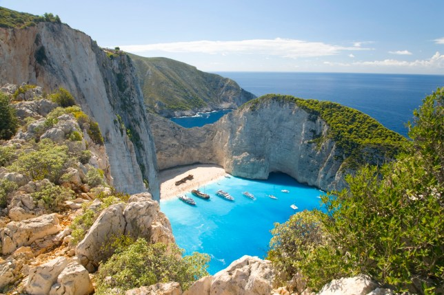 GREECE - View from clifftop over the turquoise waters of Navagio Bay (aka Shipwreck Bay, Smugglers Cove), pleasure boats anchored off the beach, near Anafonitria, Zakynthos (aka Zante, Zakinthos), Ionian Islands, Greece, Europe.