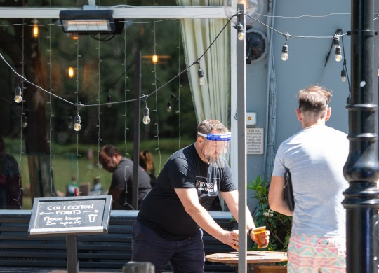 Staff serve takeaway drinks outside the Althorp pub, in Wandsworth, London, after the introduction of measures to bring the country out of lockdown. PA Photo. Picture date: Friday May 22, 2020. See PA story HEALTH Coronavirus. Photo credit should read: Dominic Lipinski/PA Wire