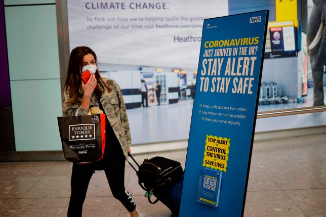 A newly arrived passenger wearing a face mask as a precaution against the novel coronavirus walks past a sign at Heathrow airport, west London, on May 22, 2020 with the British government's new 'Stay Alert' message on it. - Travellers arriving in Britain will face 14 days in quarantine from next month to prevent a second coronavirus outbreak, the government announced on Friday, warning that anyone breaking the rules faced a fine or prosecution. (Photo by Tolga Akmen / AFP) (Photo by TOLGA AKMEN/AFP via Getty Images)