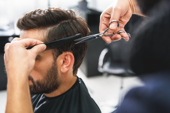 Close up of hairdresser arms cutting and combing male hair