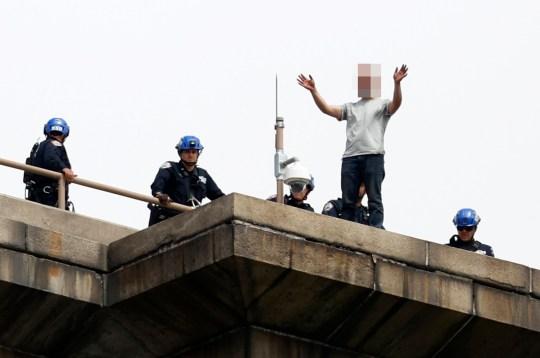 epa08438215 New York City Police officers talk to a man who climbed atop the Brooklyn Bridge in Brooklyn, New York, USA, 22 May 2020. EPA/Jason Szenes