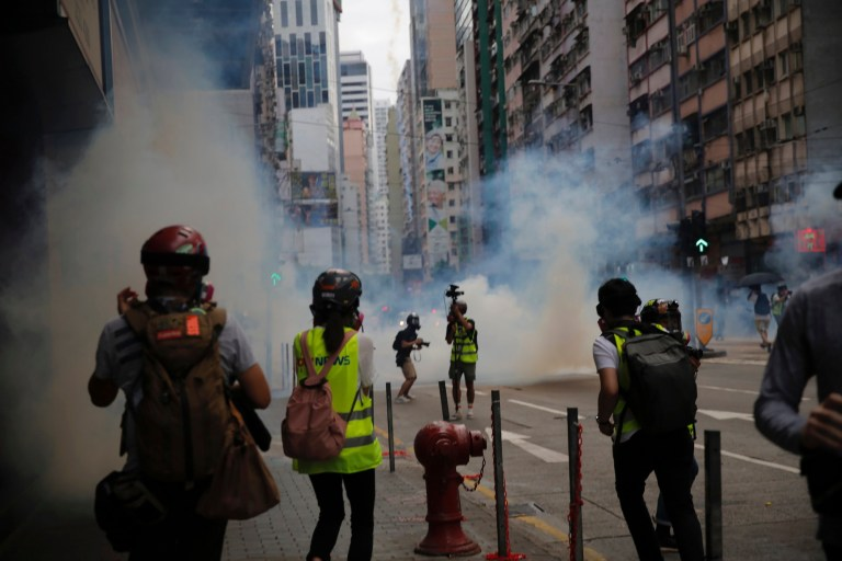 Members of the media take cover as police fire tear gas during a protest against Beijing's national security legislation in Causeway Bay in Hong Kong, Sunday, May 24, 2020. Hong Kong police fired volleys of tear gas in a popular shopping district as hundreds took to the streets Sunday to march against China's proposed tough national security legislation for the city. (AP Photo/Kin Cheung)