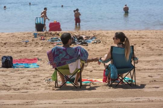 Les gens prennent le soleil sur la plage de Las Teresitas dans l'île espagnole de Tenerife, Canry, le 25 mai 2020, le premier jour après la réouverture des plages dans certaines parties du pays après des mois de fermeture. - Les régions comptant un peu moins de la moitié des quelque 47 millions d'habitants espagnols entraient dans la deuxième phase du processus de démantèlement en trois étapes qui devrait s'achever fin juin. (Photo par DESIREE MARTIN / AFP) (Photo par DESIREE MARTIN / AFP via Getty Images)