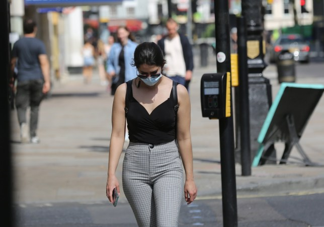 LONDON, UNITED KINGDOM - MAY 25: A woman wearing a face mask as a precaution against Coronavirus (Covid-19) walks past traffic lights in London, England on May 25, 2020. (Photo by Ilyas Tayfun Salci/Anadolu Agency via Getty Images)