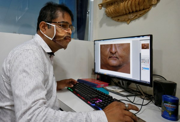 A man designs a face mask with the photograph of a customer printed on it, amid the spread of the coronavirus disease (COVID-19), at a photo studio in Gandhinagar, India, May 27, 2020. REUTERS/Amit Dave