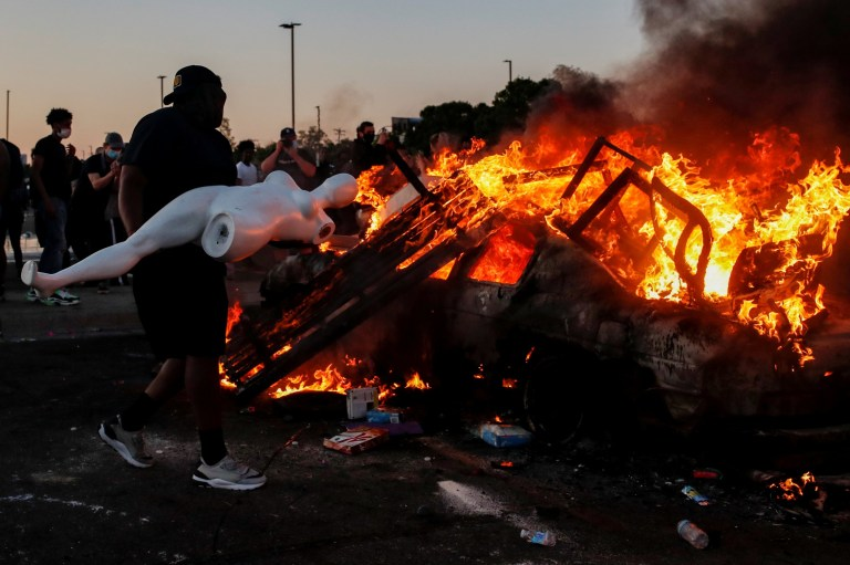 A man prepares to throw a mannequin onto a burning car at the parking lot of a Target store during protests after a white police officer was caught on a bystander's video pressing his knee into the neck of African-American man George Floyd, who later died at a hospital, in Minneapolis, Minnesota, U.S., May 28, 2020. REUTERS/Carlos Barria TPX IMAGES OF THE DAY