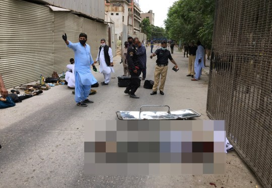 SENSITIVE MATERIAL. THIS IMAGE MAY OFFEND OR DISTURB The bodies of two men lie on the ground as police officers and security members work at the site of an attack outside Pakistan Stock Exchange in Karachi June 29, 2020. REUTERS/Akhtar Soomro