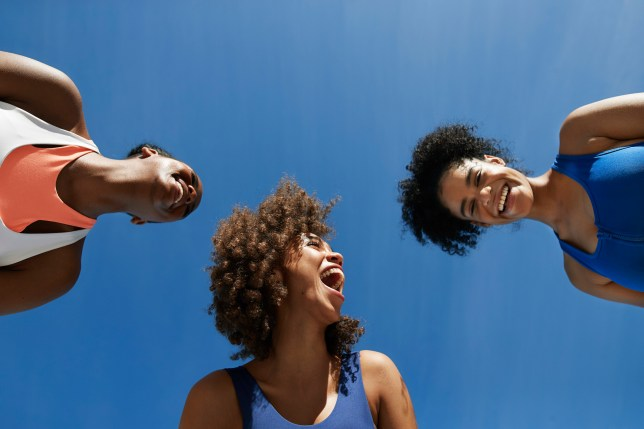 Cheerful female athletes in sportswear against blue sky