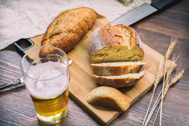 Table with fresh sliced bread on cutting board and glass of beer
