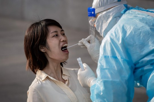 TOPSHOT - A medical worker wearing full protective gear takes a swab sample from a journalist to be tested for the COVID-19 coronavirus, nine hours before the press conference of China's Foreign Minister Wang Yi during the National People's Congress (NPC) in Beijing on May 24, 2020. - All journalists accredited to cover the CPPCC and National People's Congress events have to pass the COVID-19 test. (Photo by NICOLAS ASFOURI / AFP) (Photo by NICOLAS ASFOURI/AFP via Getty Images)