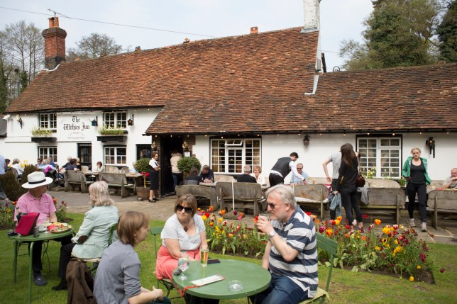 Customers in the garden at The Withies Inn traditional country pub in Compton, Surrey, UK. This public house with tiled roof dates from the 16th century. (Photo by In Pictures Ltd./Corbis via Getty Images)