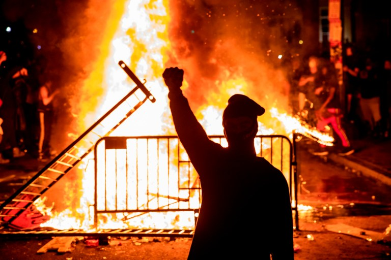 Un manifestant lève un poing près d'un incendie lors d'une manifestation à l'extérieur de la Maison Blanche sur la mort de George Floyd aux mains de la police de Minneapolis