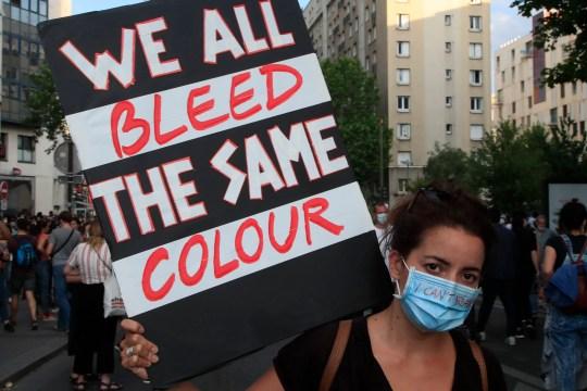 Un manifestant tient une affiche lors d'une manifestation mardi 2 juin 2020 à Paris. Des milliers de personnes ont défié une interdiction de police et ont convergé vers le palais de justice principal de Paris pour une manifestation de solidarité avec les manifestants américains et dénoncer la mort d'un Noir en garde à vue française. La manifestation a été organisée en l'honneur du Français Adama Traoré, décédé peu après son arrestation en 2016, et en solidarité avec les Américains manifestant contre la mort de George Floyd. (Photo AP / Michel Euler)