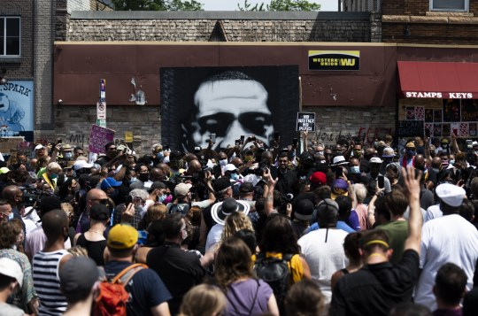 MINNEAPOLIS, MN - JUNE 2: A painting of George Floyd stands behind a group of people gathered at a memorial on the block where he was killed by police on June 2, 2020 in Minneapolis, Minnesota. A group of clergy marched to the site to give prayers and call for justice. (Photo by Stephen Maturen/Getty Images)