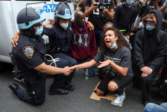 Mandatory Credit: Photo by William Volcov/REX (10667646c) A woman convinces two NYPD officers kneel along with protesters and after hugging, she was quite disgusted with the other officers who refused to do kneel, and punched the glass of the vehicle and was immobilized and detained in Soho Black Lives Matter protest, New York, USA - 02 Jun 2020