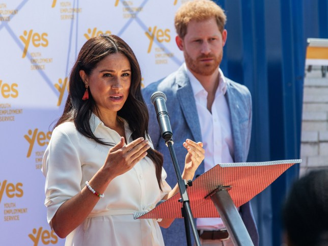Meghan Markle, Duchess of Sussex(L), is watched by Britain's Prince Harry, Duke of Sussex as she speaks at the Youth Employment Services Hub in Tembisa township, Johannesburg.