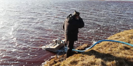 A rescuer pumping out pollutions from a large diesel spill in the Ambarnaya River outside Norilsk (Photo by YURI KADOBNOV/Marine Rescue Service/AFP via Getty Images)