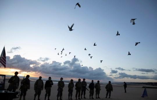 Des hommes vêtus d'un uniforme vintage américain de la Seconde Guerre mondiale regardent les pigeons sortir lors d'une cérémonie du 76e anniversaire du débarquement à Saint Laurent sur Mer, Normandie, France.