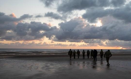Les gens en vintage US WWII uniformes marchent au lever du soleil avant une cérémonie du 76e anniversaire du débarquement à Saint Laurent sur Mer, Normandie, France.