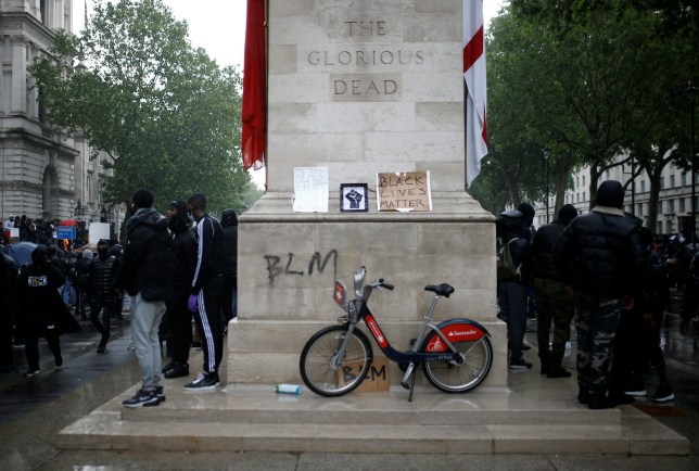 Demonstrators stand beside graffiti on the Cenotaph war memorial on Whitehall during a Black Lives Matter protest in London, following the death of George Floyd who died in police custody in Minneapolis, London, Britain, June 6, 2020. REUTERS/Henry Nicholls