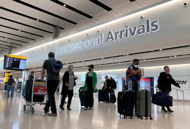 Travellers are seen wearing protective face masks at Heathrow Airport