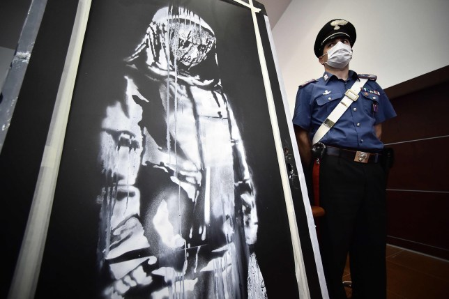 A policeman stands guard near a piece of art attributed to Banksy, that was stolen at the Bataclan in Paris in 2019, and found in Italy, ahead of a press conference in L'Aquila on June 11, 2020. - The work was found in an abandoned farmhouse in Abruzzo, l'Aquila prosecutor informed on June 10, 2020. (Photo by Filippo MONTEFORTE / AFP) / RESTRICTED TO EDITORIAL USE - MANDATORY MENTION OF THE ARTIST UPON PUBLICATION - TO ILLUSTRATE THE EVENT AS SPECIFIED IN THE CAPTION (Photo by FILIPPO MONTEFORTE/AFP via Getty Images)