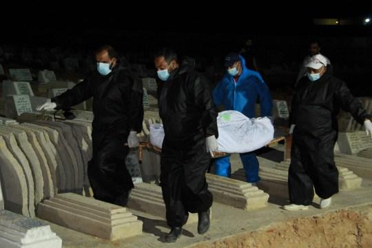 Les employés du cimetière portent des masques faciaux lors de l'enterrement des corps d'immigrants africains, morts noyés et rejetés par la mer après le naufrage de leur bateau devant l'île de Kerkennah, le 11 juin 2020, au cimetière de Sfax. (Photo par HOUSSEM ZOUARI / AFP) (Photo par HOUSSEM ZOUARI / AFP via Getty Images)