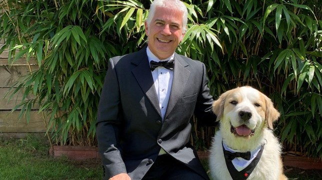 Boomer the therapy dog and his owner posing for the camera in tuxedo suits.