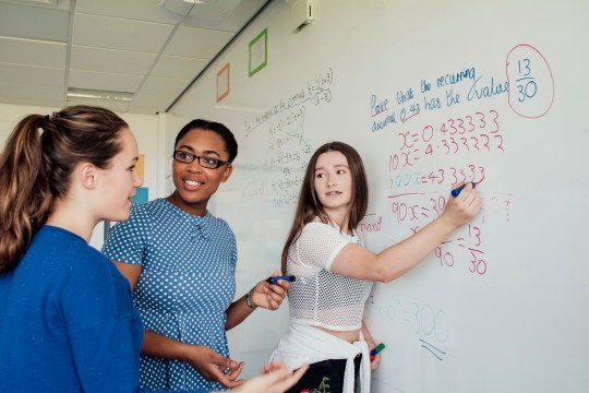 Teenagers asking for help from the teacher within mathematics class.