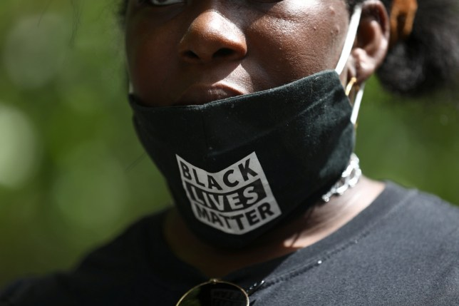 A demonstrator attends a Black Lives Matter protest wearing a face mask that says Black Lives Matter