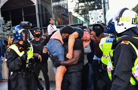 A protester carries an injured counter-protester to safety, near the Waterloo station during a Black Lives Matter protest following the death of George Floyd in Minneapolis police custody, in London, Britain, June 13, 2020. REUTERS/Dylan Martinez