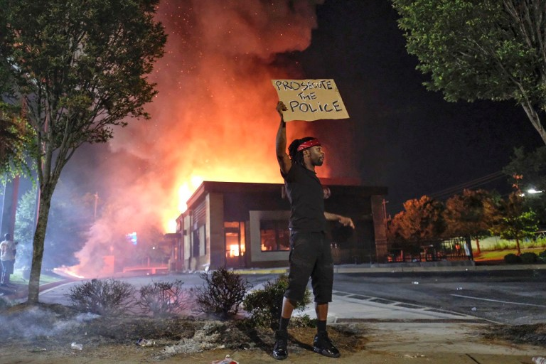 A person holds a sign as a Wendy's restaurant burns Saturday, June 13, 2020, in Atlanta after demonstrators set it on fire. Demonstrators were protesting the death of Rayshard Brooks, a black man who was shot and killed by Atlanta police Friday evening following a struggle in the Wendy's drive-thru line.