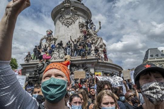 Les manifestants se tiennent sur le monument de la place de la République lors d'une manifestation contre le racisme le 13 juin 2020 à Paris, France.