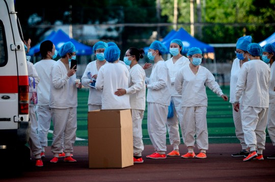 Medical personnel wearing protective suits gather at the Guang'an Sport Center before a swab test for people who visited or live near Xinfadi Market in Beijing on June 14, 2020. - The domestic COVID-19 coronavirus outbreak in China had been brought largely under control through strict lockdowns that were imposed early this year -- but a new cluster has been linked to Xinfadi market in south Beijing. (Photo by NOEL CELIS / AFP) (Photo by NOEL CELIS/AFP via Getty Images)