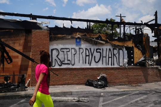 A woman uses her cell phone to document the damage to a burned Wendys restaurant on the second day following the police shooting death of Rayshard Brooks in the restaurant parking lot June 14, 2020, in Atlanta, Georgia. - The fatal shooting of a black man by a white police officer, this time in Atlanta, Georgia, poured more fuel June 14, 2020 on a raging US debate over racism after another round of street protests and the resignation of the city's police chief. A Wendy's restaurant where 27-year-old Rayshard Brooks was killed was set on fire June 13, 2020 and hundreds of people marched to protest the killing. (Photo by Elijah Nouvelage / AFP) (Photo by ELIJAH NOUVELAGE/AFP via Getty Images)
