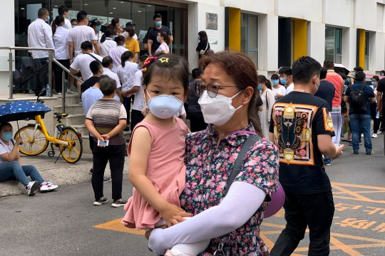 A woman and a child wearing protective face masks to help curb the spread of the new coronavirus walk by people lining up outside a health center to get the nucleic acid test in Beijing, Monday, June 15