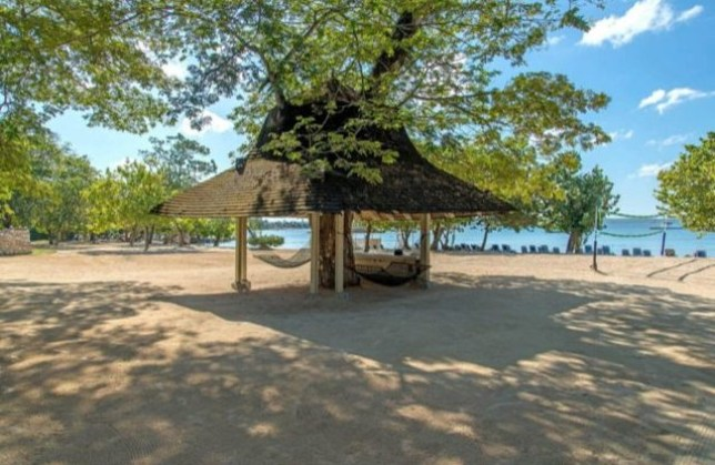 Wide shot of a Jamaican beach with a hammock seen in the background under an outdoor cabana