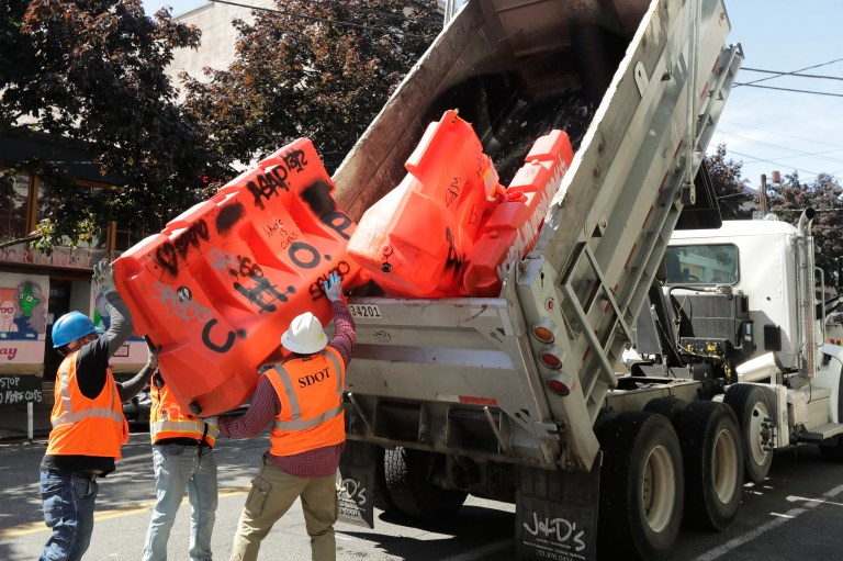 City of Seattle workers load a plastic barricade that has CHOP written on it, Tuesday, June 16, 2020, into a dump truck at the Capitol Hill Occupied Protest zone in Seattle. The barricades were replaced Tuesday with heavier concrete and wood barriers designed to mark separate areas for people and cars in the area of the city's Capitol Hill neighborhood near the department's East Precinct police station that has been taken over by protesters after violent clashes with police. (AP Photo/Ted S. Warren)