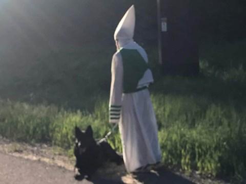 Man seen walking dog and waving at cars in KKK hood