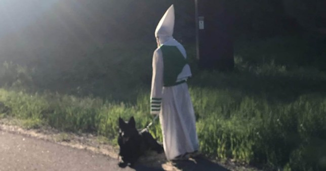 Man wearing a KKK hood on a dog walk