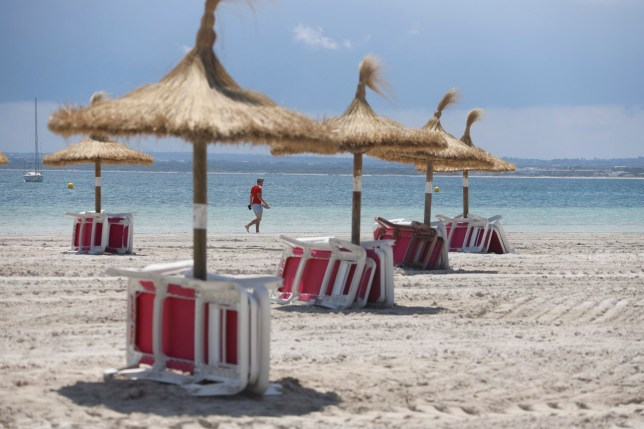ALCUDIA, MALLORCA, SPAIN - JUNE 18: A tourist walks on Alcudia beach on June 18, 2020 in Alcudia, Mallorca, Spain. From June 15, approximately 10,900 holidaymakers from Germany are expected to arrive in the Balearic Islands, this is a pilot plan by the Spanish Government to gradually open tourism following the Coronavirus (COVID-19) pandemic . (Photo by Clara Margais/Getty Images)