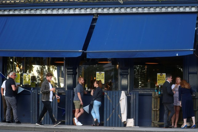 People drink alcohol outside a pub serving takeaway beer, in London