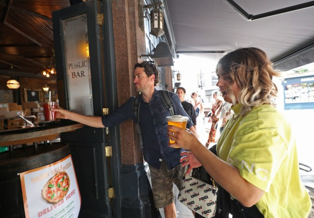 Customers are served takeaway drinks from the Cat & Mutton pub in Broadway Market, London, as further restrictions are lifted to bring England out of the coronavirus lockdown. PA Photo. Picture date: Sunday June 21, 2020. See PA story HEALTH Coronavirus. Photo credit should read: Yui Mok/PA Wire