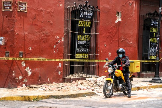 A motorcyclist rides past security tape alerting of a damaged building after a quake in Oaxaca, Mexico on June 23, 2020. - A 7.1 magnitude quake was registered Tuesday in the south of Mexico, according to the Mexican National Seismological Service. (Photo by PATRICIA CASTELLANOS / AFP) (Photo by PATRICIA CASTELLANOS/AFP via Getty Images)