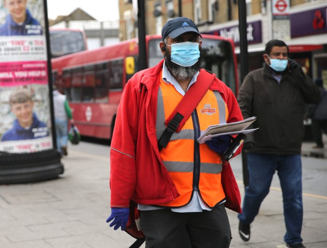 A postman wearing protective personal equipment walks through East Ham, London, as the UK continues in lockdown